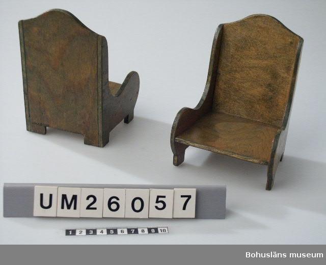 Möbel till dockskåp. Grönbetsade, svängda sidostycken, hög rygg.  Se kommentar UM026053 Släkt- och personuppgifter se UM026024