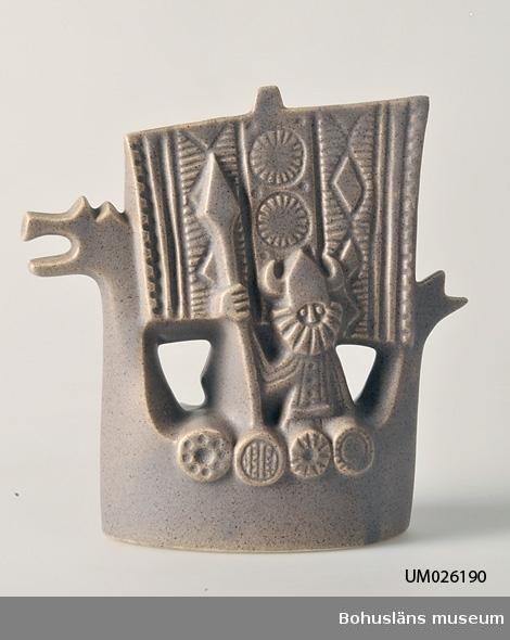 """Stiliserat vikingaskepp med drakhuvud och fyrkantigt segel med geome risk dekor. Vid relingen en viking med spjut och hjälm med horn. Vardera sidan likadan så när som på att seglet har olika geometrisk dekor. Jämnt pålagd ljust brungrå glasyr. I botten märkt med svag relief """"SYCO - SWEDEN"""" samt """"1456"""". Numret troligen ett artikelnummer. Under semestervistelse i sin sommarstuga i Hasslevik vid Malö strömmar gjorde familjen en utflykt till Mollösund. Där hade SYCO försäljning i ett magasin (c:a 1960). Givaren som då var c:a 15 år köpte några fyrkantiga tallrikar samt denna prydnadsfigur, som sedan dess följt henne i olika bostäder fram till gåvodagen. Se bilaga med givarens beskrivning. Förvärvsort, se Värde."""