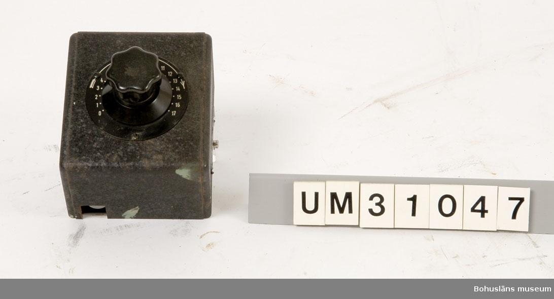 Volymreglage av svart brännlackerad plåt för väggmontering, troligen till ljudanläggningen.  Rektangulär låda märkt med metallskylt: KLANGFILM G. m. b. H. Mittpå en rund vridbar ratt av bakelit på platta för nivå märkt med siffrorna 1 t o m 17.  Skåpet har använts tillsammans med  projektor UM31031.   Projektorn är tillverkad av AEG på 1920-talet och har använts i Folkets Hus i Sjöbol vid Lysekil.  Till projektorn hör en lång rad delar och olika tillbehör, UM31031 - UM31062.  För ytterligare upplysningar om filmprojektorn, dess olika delar och användning, se UM31031.