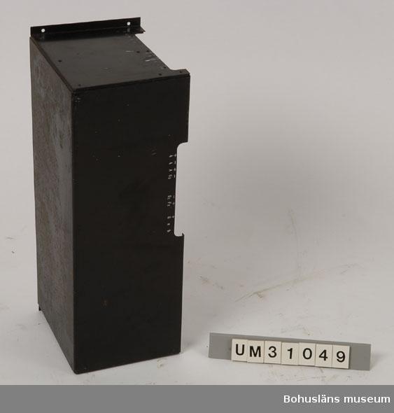 Svartlackerad skyddsplåt för väggmontering med oklar användning.  På långsidan och vänster kortsida märkt med vita siffror och bokstäver i någon slags graderad skala. Möjligen använt som väggskåp som dolde ljusknapparna i projektorrummet på Folkets Hus i Sjöbol.  Har använts tillsammans med  projektor UM31031.   Projektorn är tillverkad av AEG på 1920-talet och har använts i Folkets Hus i Sjöbol vid Lysekil.  Till projektorn hör en lång rad delar och olika tillbehör, UM31031 - UM31062.  För ytterligare upplysningar om filmprojektorn, dess olika delar och användning, se UM31031.