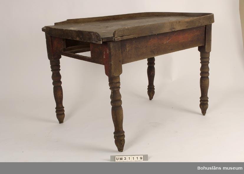 Skansbord med en rak bakre kortsida och rundad främre kortsida. Hög slingerkant runt hela bordskivan. Svarvade ben, urtag för låda, låda saknas. Originalskick med rester av rödfärg på några ställen.