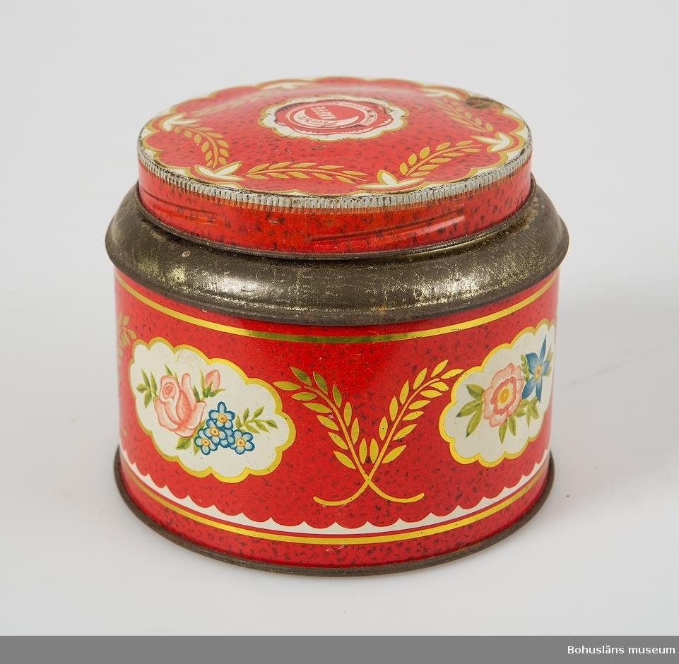 """Rund plåtburk med lock. På utsidan dekor av påtryckta blommor och ax mot röd botten och detaljer av guld. På locket påtryck varumärke med texten: """"KärnKAFFE kaffet med arom""""."""