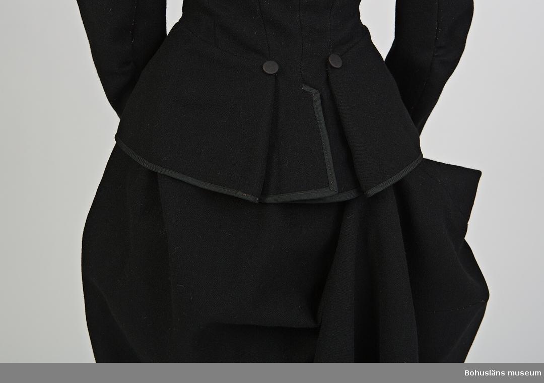 Svart lång kjol sydd i kypertvävt ylletyg. Del av riddräkt UM62.04.001 - UM62.04.007 Kjolen är oregelbundet formad. Längsta delen på höger baksida är längst. Vid användning häktas denna upp med hjälp av en hake och en sydd hank (skadad). Enkel bandkantad linning med hyske och hake samt snedställd öppning som knäppes av fyra tygklädda knappar. Samma typ som i jackan.  Fållens uppvikta kant är sicksackklippt samt uppsydd med maskinsöm. Mer information se UM62.04.001