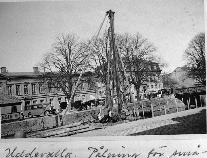 """Text på kortet: """"Uddevalla. Pålning för småbåtar"""".  Enligt tidigare noteringar: """"Uddevalla, Bäveån mellan hamngatorna, pålning för småbåtar. På Norra Hamngatan buss och hästdroska. Repro 1984 av foto"""