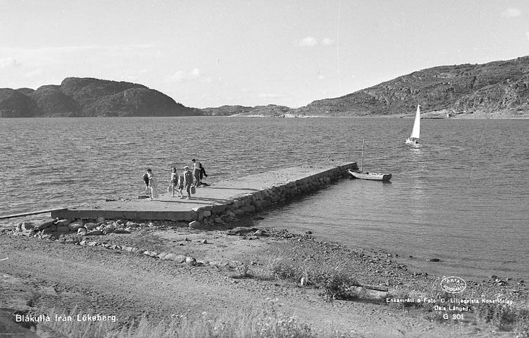 """Enligt AB Flygtrafik Bengtsfors: """"Lökeberg sjön m. bryggan Bohuslän"""". Enligt text på fotot: """"Blåkulla från Lökeberg""""."""