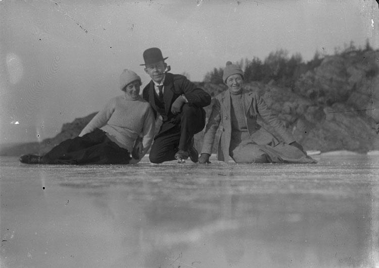 """Enl. text i blå bok: """"Tre skridskoåkare sittande på isen."""" ::"""