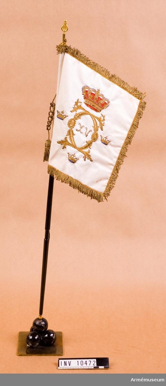 Grupp B I. Gåva till Anton Edvin Olsson. Orginalet broderat av Drottning Lovisa överlämnat till förbandet den 3 maj 1863. Gåva från fru Lydia Olsson, Stockholm till AM. Standaret har en stång. Standaret är tillverkat i skala 1:3.