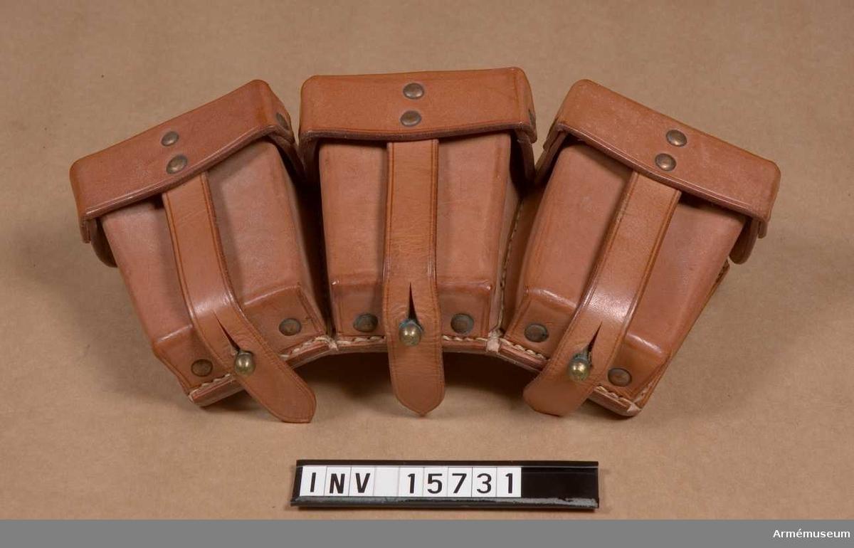 """Grupp C I. Patronväska av läder i naturfärg, med tre skilda avdelningar med lock, som stänges med remmar och knappar: på baksidan finns: två remmar för att fästa väskan vid livremmen och en ring av gulmetall för att sammankoppla väskan med tornistens axelrem. I varje väskans avdelning rymmes två patronknippen (a 5 patroner) och i hela väskan 30 patroner. Patroner för ryskt gevär modell år 1891. På väskans baksida finns en stämpel på vilken det står: """"K.V.S.T."""" , """"I.XI. - 1935"""". Alla metalldelar av gulmetall."""