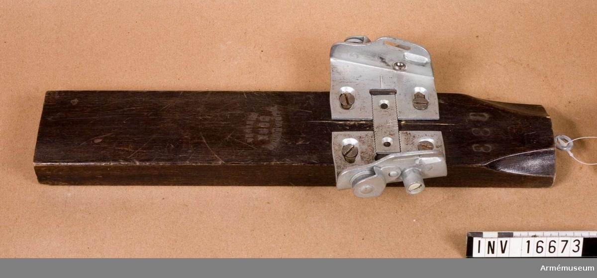 """Skidbindning vänster, typ Divoli. Hellängd och vikt med monteringskloss. Tvådelat tåjärn märkt """"V"""" och  med tre kronor. Metalldelarna är av varmförzinkat stål. Monteringskloss av trä, märkt med tre kronor och """"333 skidfabriken Bore Freluga""""."""