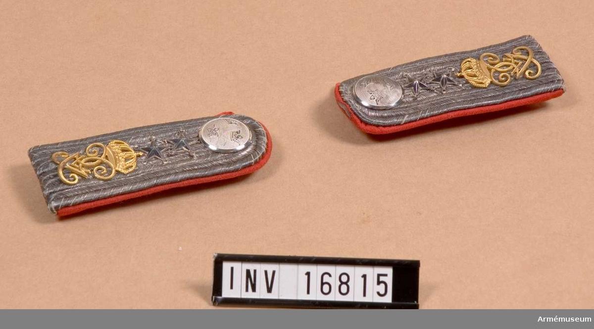 Till vapenrock att fästas i därför avsedda hällor på axlarna. Med matta och foder av rött kläde samt med knapp i silver m/1792 av större modellen samt beläggningssnören av silver. Konung Gustav V:s namnchiffer i guld.