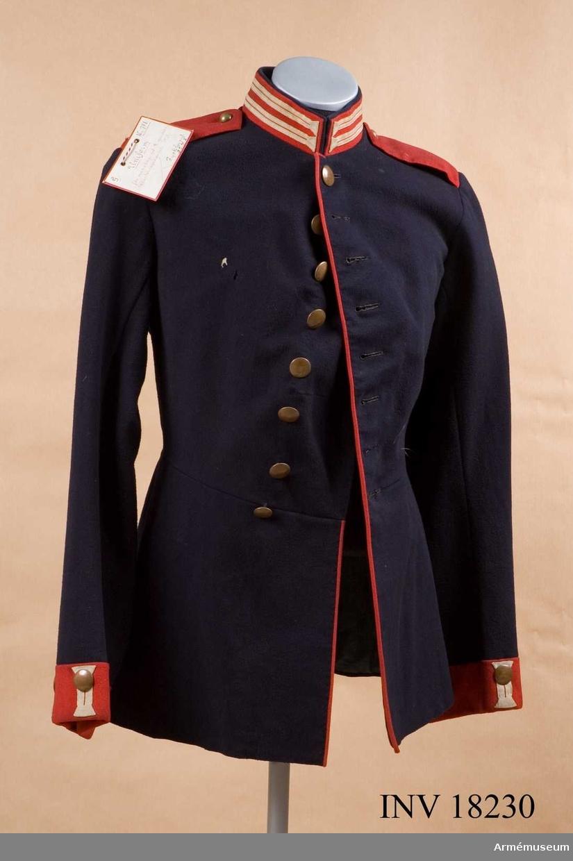 """Grupp C. Ur uniform för manskap vid 2:a Gardesdragonregementet, kejsarinnan Alexandra 1840-70-talet. Består av hjälm, vapenrock, livrem, byxor, stövlar, patron- väskor, bajonetthylsa. Vapenrock av mörkblått tyg, 69 cm lång, åtsittande med tvärsöm i midjan. Rocken är enradig och har åtta knappar, På båda bak- fickorna ett tvåuddigt lock, vartdera med tre knappar. Axelklaffar av rött tyg, med mörkblått undertyg. Längd 14 cm, bredd 6 cm. Axelklaffarna är fastsydda vid ärmsömmarna och fästade vid rocken med knappar. Den vänstra axeln har kullriga vid rocken med knappar. Den vänstra axeln har kullriga knappar- de passar inte till denna vapenrock- och den högra har knappar med kompaninummer (""""9""""). Fodret är av grov linnelärft på övre delen medan den nedre är av svart grovt satängtyg. På bröstet finns två band av grov linnelärft. Där finns även en stämpel: """"II.G.R."""" (Andra Gardesregementet).  Knappar av koppar, 2 cm i diameter. Bröstet, fickorna och ärm- uppslagen har knappar av större modell, på axlarna finns mindre knappar. Alla knappar har kompaninummer. Krage- upprättstående med raka vinklar av rött tyg med blå  passpoal på kragens övre kant. Kragen är på båda sidor försedd  med två (1 cm breda) """"knapphål"""" av vita bomullsband (beteckning för Gardestrupper). Den har tre hyskor och hakar och är fodrad med mörkblått tyg. Passpoaler- röda längs rockens främre kant och de bakre fickornas lock. Ärmuppslag (svensk modell), rakskurna av rött tyg, 6 cm höga med två knapphål av vita bomullsband, 5,5 cm långa och 2 cm breda. LITT  Uniformenkmunde, Richard Knötel. Album. Preussen. Färgbild av regementsuniform för 2:a Gardesregementet till fot år 1843.  Geschichte der Bekleidung und Ausrüstung der Königlichen Preussischen Armée in Jahren 1808 bis 1878. Sidan 3 paragraf 372. Vapenrockens utveckling i tyska armén. Denna vapenrock infördes i oktober 1842 (m/1843). Das Deutsche Reichsheer. G.Krickel. Sidan 11. Beskrivning av vapenrock för gardestrupper. Det 2:a Gardesregementet till fo"""