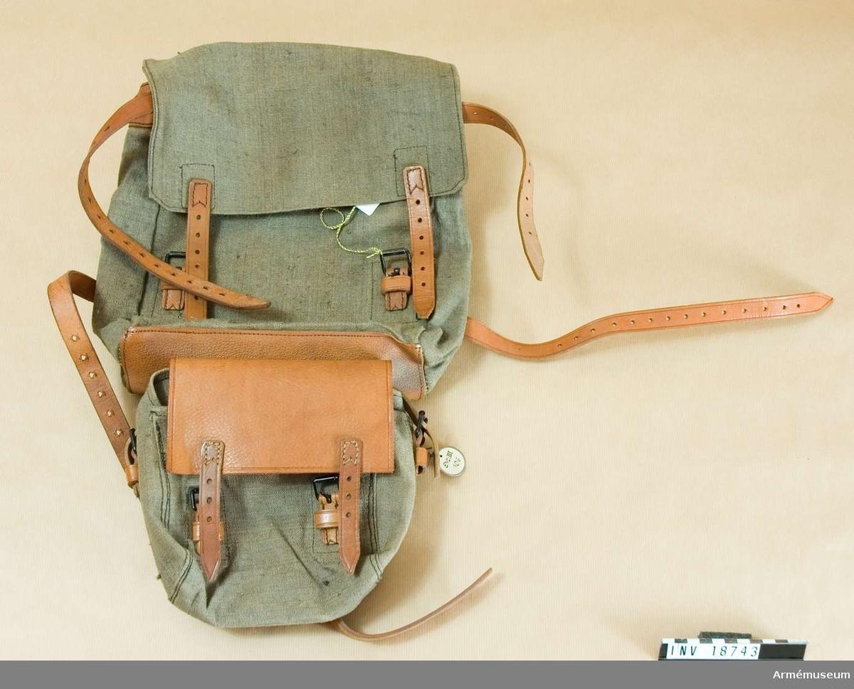 """Grupp C I Uniformen består av vapenrock, ridbyxa, uniformsmössa m/1912, kappa m/1912, benlindor, kängor, tornister, livrem, patronväskor, ränsel med väska. Av kakifärgat tjockt tyg. Två skilda ryggsäckar, övre och nedre, som sammankopplas med med remmar. Alla remmar av ljusbrunt läder med järnspännen.  ÖVRE säcken har l:250 mm, b:80 mm, h:300 mm.  Stänges med två  par remmar och spännen. På lockets baksida en stämpel """"C.M. 1915"""". Två bärremmar är fastsydda på säckens baksida för koppling till livrem. Två par remmar på sidorna och en rem på övre delen för att binda fast överrock och tält.  NEDRE säcken har l:170, b:70, h:180 mm. Lock av brunt läder. Stänges med två remmar och järnspännen. Säcken är fastknäppt till den övre med två remmar.  Samhörande nr är AM.18734-43, 20138"""