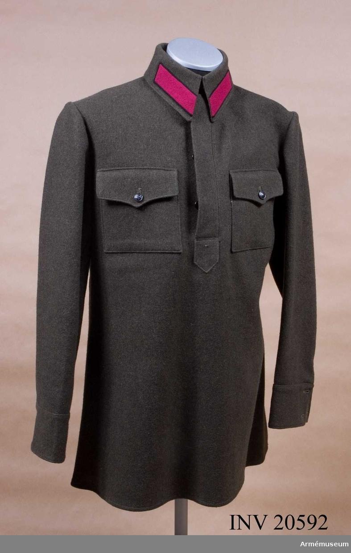 """Vapenrock för menig vid infanteriet, Ryssland. 1925. Grupp C I. Samhörande mössa. Vapenrock (blus), skjortmodell av mörkgrönt kläde knäppt med tre knappar. Två fickor med lock på vardera sidan. Locken knäppes med två svarta sovjetknappar. Knappar, svarta, sovjetmodell med hammare och skära. Krage av mörkgrönt kläde med klaffar av körsbärsrött kläde med svart passpoal. Kragen fodrad med grönt tyg, sammanfäst med två hyskor och hakar. Ärmuppslag av mörkgrönt kläde med sprund, vilket knäppes med två svarta  sovjetknappar. På skjortan finns en tyglapp, på vilken står på svenska  """"Moskva"""" """"Fabriken N 10, Moskva verkstad"""" benämning 5 tyg 757, standard N 260, Fason N 260, Storlek 52, Längd 3, prislista 703 partipris 71,40, chiffer 6885. Vidare finns en kartonglapp med rysk text; se bilaga. LITT  Knötel-Sieg, Handbuch der Uniformenkunde, sida 341: Det körsbärsröda klädet i uniformen är ett kännetecken för infanteriet eller den högre staben."""