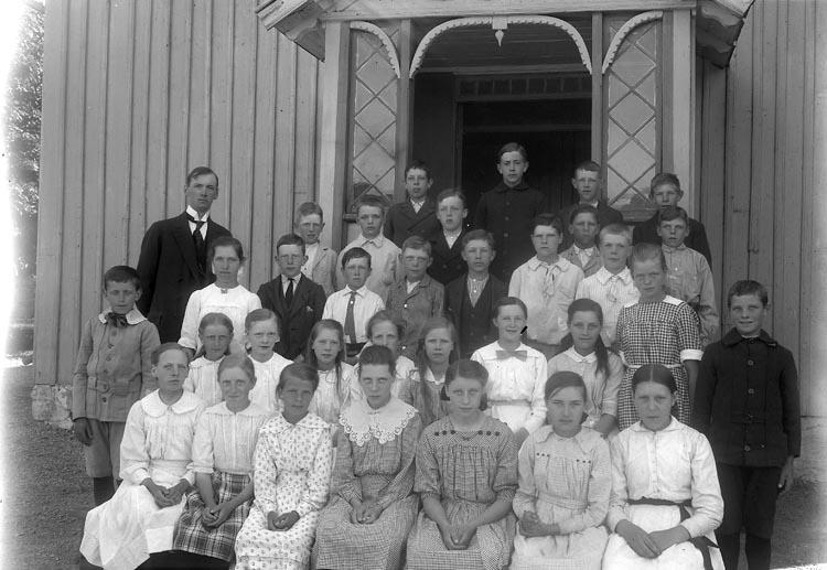 """Enligt fotografens journal nr 4 1918-1922: """"Folkskolan i Kyrkenorum Här"""". Enligt fotografens notering: """"Folkskolan Kyrkenorum, lärare Ivar Larsson med elever. (Organist i Norums kyrka)""""."""