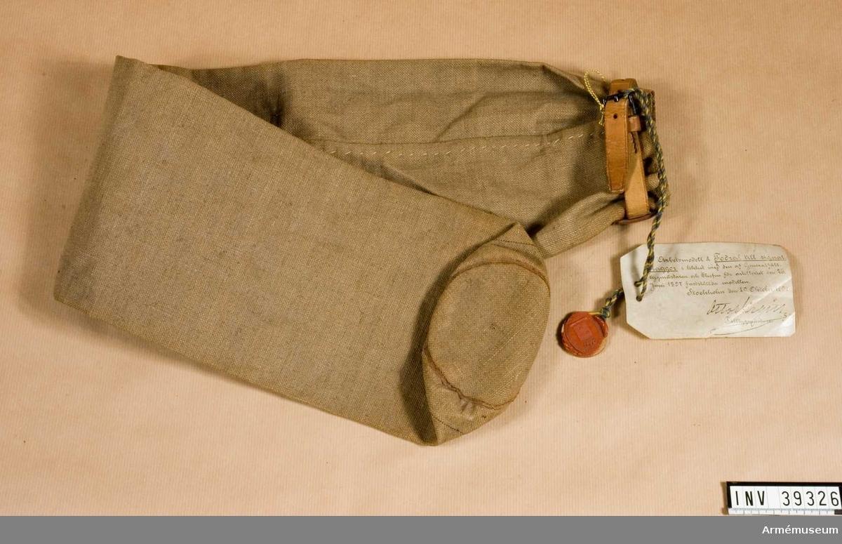 Grupp H III.  Arbetsmodell m/1897 med modellapp.Av bomullstyg, s.k. smärting. Längst upp på fodralet löper en läderrem för tillslutning.