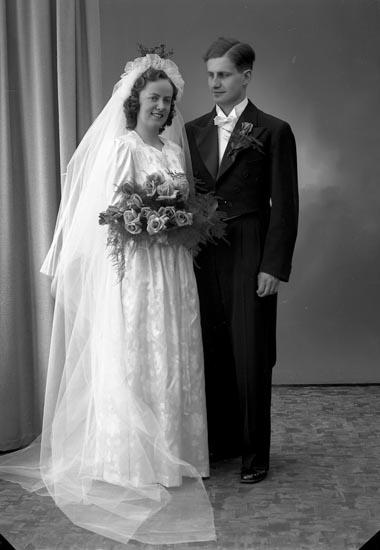 """Enligt fotografens journal nr 7 1944-1950: """"Happ, Brudpar Olsson, Jarlsg. 12 Uddevalla""""."""