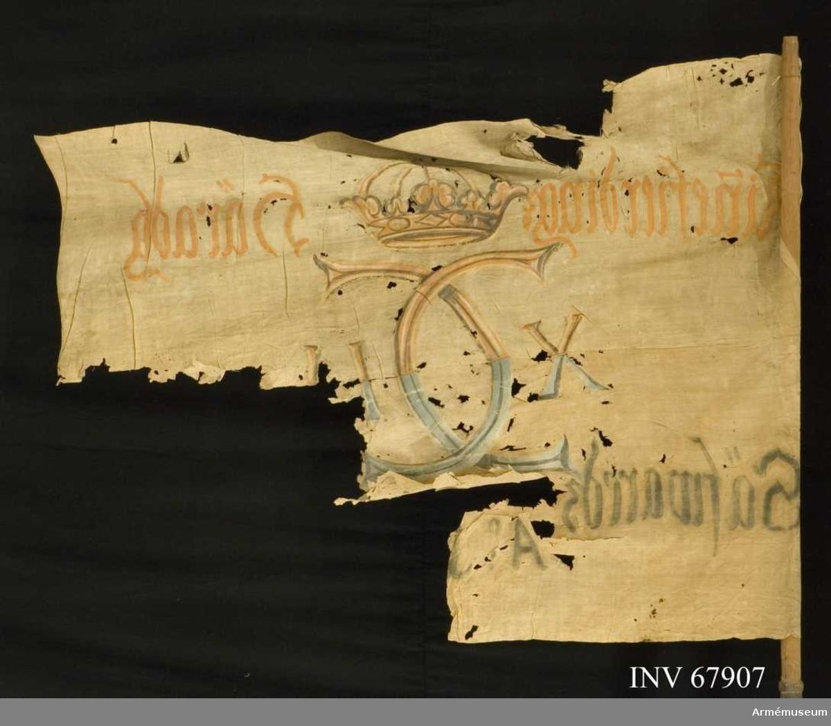 Duk: Tillverkad av enkel vit linnelärft, sydd av två horisontella våder.  Dekor: Målad från dukens båda sidor, Karl XII:s namnchiffer dubbelt C med på ömse sidor XII. Krönt med sluten krona, upptill i gult och brunt, nedtilll i blått och svart. Text på ömse sidor om chiffret; upptill i gult, nedtill i svart.   Stång av trä. Nedre delen svartmålad.