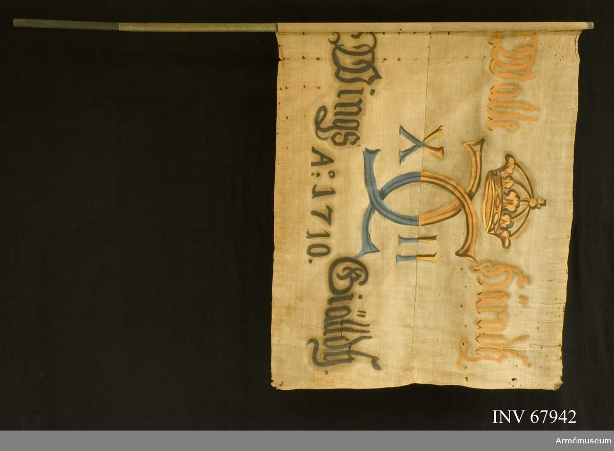 Duk: Tillverkad av enkel vit linnelärft, sydd av två horisontella våder. Duken fastspikad vid stången med handsmidda järnspikar på en liten läderremsa.   Dekor: Målad endast från dukens insida, i mitten Karl XII:s namnchiffer dubbelt C med XII på ömse sidor, krönt med sluten krona, i gult och brunt i det övre fältet och blått och svart i det nedre. Text på ömse sidor om chiffret; upptill i gult, nedtill i svart.  Stång av furu.