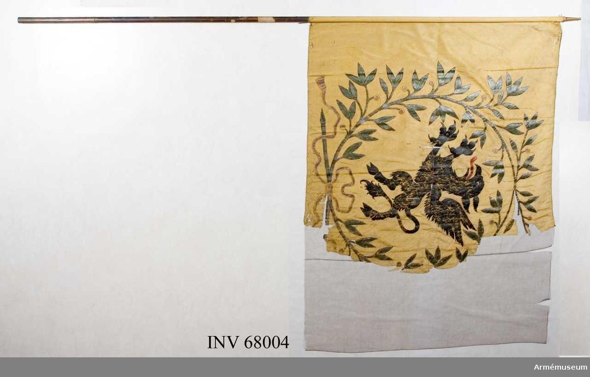 Duk Enkel, tillverkad av gul taft, sydd av två horisontella våder. Kantad med rullfåll. Duken fäst vid stången med en rad tennlikor.  Dekor: Målad omvänt lika på båda sidor med Södermanlands sköldemärke, en svart grip med röd tunga omgiven av en stor krans av två lagerkvistar i silvergrönt med blad och gyllene bär, upptill och nedtill hopknuten, nedtill med rosett med långa tofsprydda ändar.  Stång: Tillverkad av brunmålad furu. Holk av mässing.  Jämför nr 16866 (AM.068009) och 16737 (AM.067895).