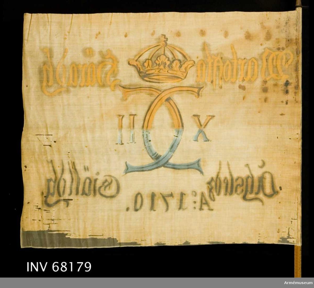 Uppbådsfana för Åsle socken i Vartofta härad.  Duk: Tillverkad av enkel vit linnelärft. Två våder horisontellt sammankastade. Kastfållen på dukens insida. Vertikala ytterfållen lagd åt dukens insida. Fäst med järnnagel på en läderremsa.  Dekor: Målad, endast på dukens insida, dock är namnchiffret och kronan ifyllt på dukens utsida. I mitten Carl XII:s namnchiffer krönt med sluten krona, dubbelt C på ömse sidor om detta X-II. På övre våden i gult och brunt, på den nedre i blått och svart.   Text på ömse sidor om chiffret, upptill i gul och nedtill i svart. Under chiffret text i svart.  Stång: Tillverkad av trä. Åttkantig. Avtagen. Metallcylinder påsatt. Järnskenor.
