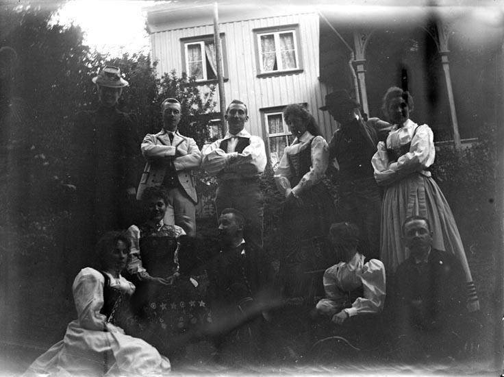 """Enligt fotografens noteringar: """"Grupp Folkdansare."""" Plats: Gustafsberg Datum: 20 Juni 1899 Tid: Kl 7.15 e.m. Ljus: Kvällsljus Bländare: No 2 Objektiv: Svenska Express Exponering: Hastighet No. 3 1/2 Framkallning: Hydrochinon, Eikonogén Anmärkningar: """"Underexponeradt!"""""""