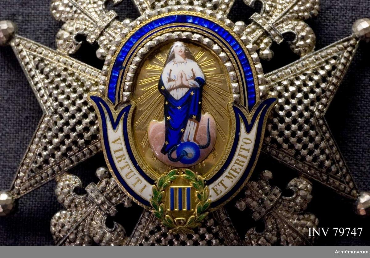 Grupp M  Kommendör 1:a klass. Ett 8-uddigt briljanterat silverkors med facetterade kulor å uddarna samt liljor mellan armarna.  I korsets mitt en oval sköld, innehållande (i upphöjt arbete) en bild av den heliga jungfrun, iförd en vit underklädnad och en blå med gyllene stjärnor beströdd mantel.  Vid hennes fot ringlar sig en orm omkring en jordglob ?, allt på en bädd av gyllene strålar.  Sköldens ram är upptill blåemaljerad mellan pärlkanter av silver, nedtill vitemaljerad och, mot sköldens mitt, delad i två flikar.  Devis: VIRTUTI ET MERITO, inskriften i gyllene bokstäver, delas av en grönemaljerad lagerkrans, inneslutande siffran III i blå emalj.