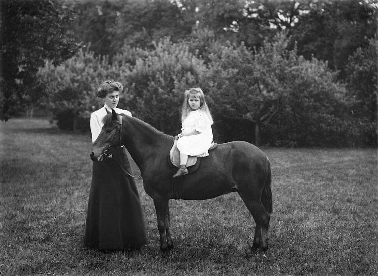"""Enligt noteringar: """"Häst med flicka på ryggen. Troligen någon av familjen Sörensens sommargäster."""" (BJ)"""