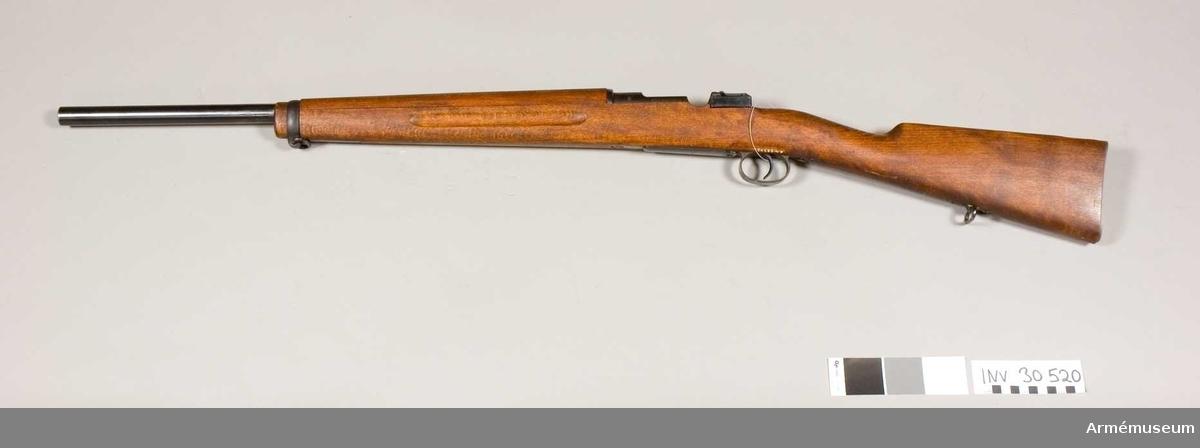 Grupp  E II f Gevär. 7,9 mm. Geväret är kamrat för svenska 8 mm kulsprutepatroner m/1932 samt har ovanligt tjock, 60 cm lång pipa. I övrigt liknar vapnet AM.022336, men har aldrig haft några siktmedel. Geväret torde ha varit avsett för ammunitionsprovning. På lådans vänstra sida står 29/34 MAX och på hävarmsknappen 26/34. På flertalet av vapnets övriga delar är numret 26 inslaget.Se även AM.030519. Tnr 27/34, 1932. ej sls.