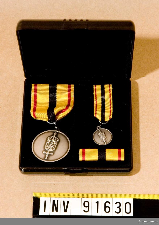 Etui innehållande medalj, minimedalj samt släpspänne. Antagligen Mellersta militärområdesstabens förtjänstmedalj. På framsidan ett vapen och på baksidan märkt med text.  Band i gult med bred svart rand på mitten och en röd rand på vardera sidan.