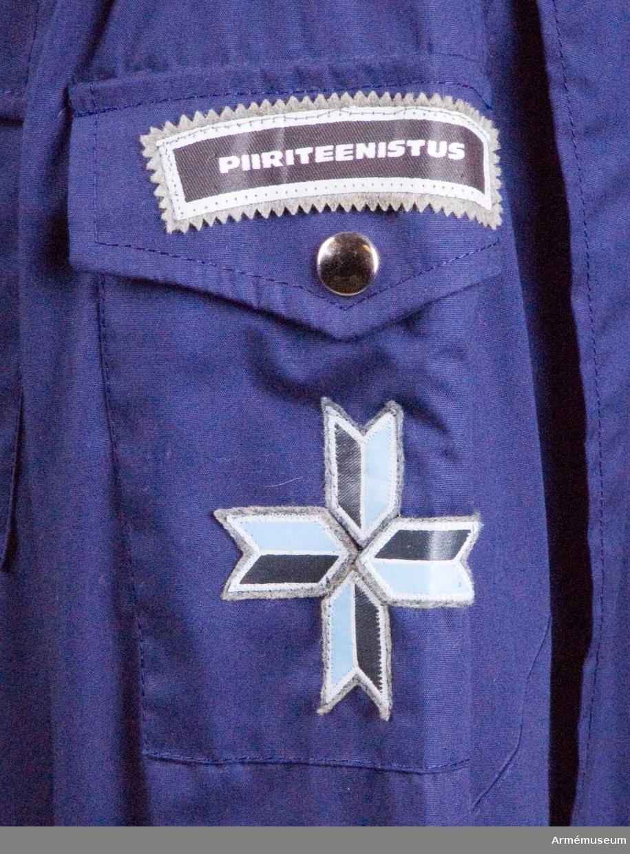 """På höger ärm: Ett tecken med uppåtriktat svärd (försvar), framför blåklint (Estlands nationalblomma). Ovanför detta """"Pärnumaa"""" = Pärnu landskap / län. På vänster ärm: Fyra pilar med spetsarna ställda mot varandra, som tillsammans bildar ett kors, anger graden överkommissarie. Piirivalve fungerar som gränspolis. Näst lägre gradbeteckning är tre pilar, som anger kommissarie. Ovan detta """"Piiriteenistus"""" = Gränstjänst. Tidigt 1990-tal."""