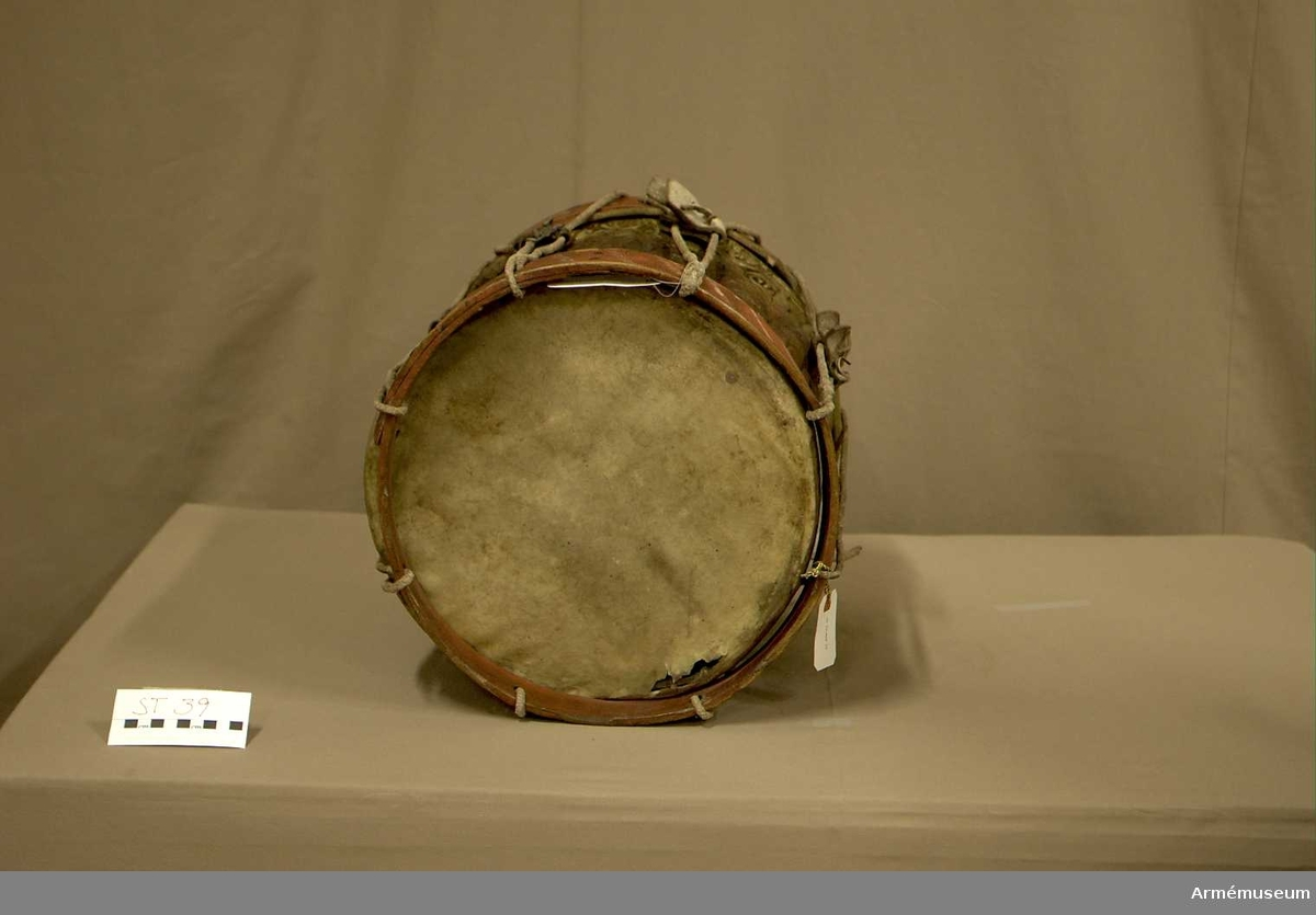 Cylindertrumma av: metall dekorerad med vapensköld.  Membran: det övre skinnet har tre sprickor och ett litet hål. Två rep är bundna i spännringen och kryssar varandra. Det undre skinnet saknas.  Veckelgjordar: av trä, rödmålade med diagonalt vitmålade streck. Den övre v.-gj. har släppt och ligger ovanpå skinnet. Den undre v.-gj. har ett fyrkantigt hål  ca 2 x 2 cm. intill sejarhållarens skruv.  Spännlina: något bristfällig med fem stycken spännstroppar i vitkalkat läder.  Utsmyckning: Danska riksvapnet med sköldhållare samt Dannebrogens och Elefantordens kedjor. Metallen skiftar från mörkbrun till ljusaste mässing. Fyra lagningar i cylinderns ornamentik Bärring: saknas   Märkning: ST TRUMMA 39 skrivet direkt på cylindern med vita tecken.  Sejarhållare: finns, med skruv.