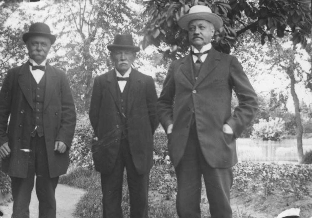 Tre män i en trädgård. Gustav Anderssons far, Johan August, längst till höger.