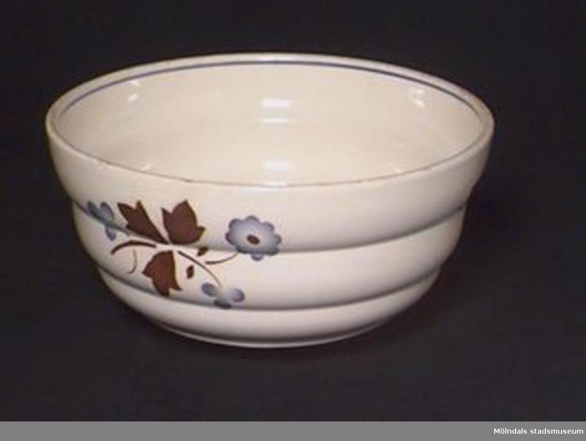 """Rund skål som vidgar sig upptill. Gulvit med blå och brun blom- och bladdekor. """"5/.0."""" i relief undertill."""