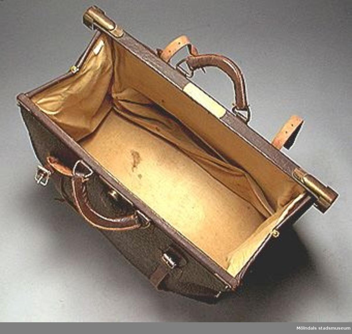Brun läderkoffert med två handtag. Mässingslås och två remmar runt med spännen. Ägaren var ärkebiskop Erling Eidems amma. Hon skänkte kofferten till givarens mor på 1930-talet.