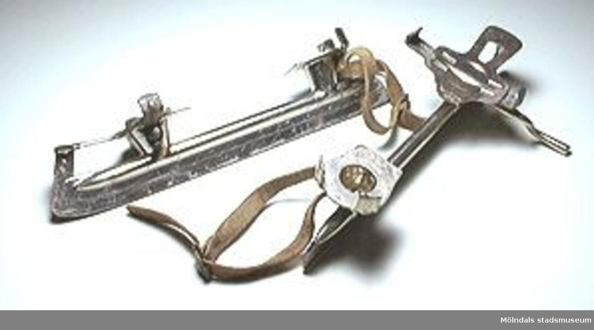 """Märkt """"OS BL D: JÄRNA 414 10 AN PAT.S.""""Skridskor helt tillverkade i helt i förnicklad metall. De skall spännas fast med en rem över kängan. Kängornas sidostöd kan skruvas ut eller dragas in med hjälp av en skruv och en vev.Skridskorna inköptes i Joel Jakobssons Järnhandel 1981 eller 1982.De har använts av givaren."""