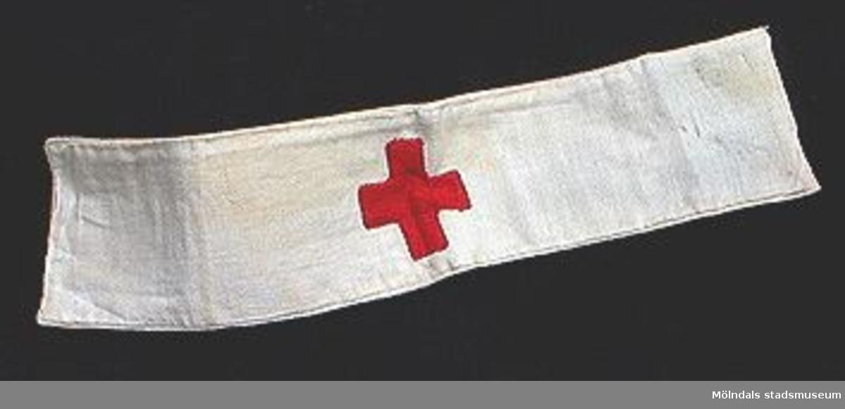 Vit armbindel av två ihopsydda vita tygremsor med ett påsytt rött kors.