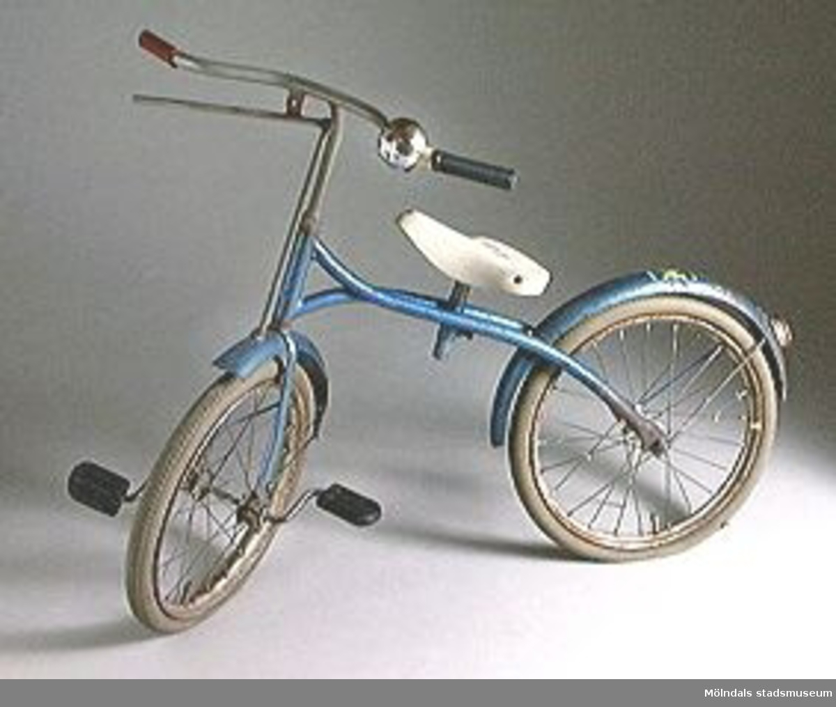 """Barncykel med blå färg, vit sadel av hårdgummi, pumpbara gummidäck, gummipedaler på framhjulet. Gummihandtag på styret, ringklocka av metall, handbroms, kattöga baktill.Klistermärke med """"K"""".Något rostig.Tidigare sakord: barncykel.Cykeln inköptes 1986 av givaren i Lopplådan, Dalbogatan 3E, Mölndal."""