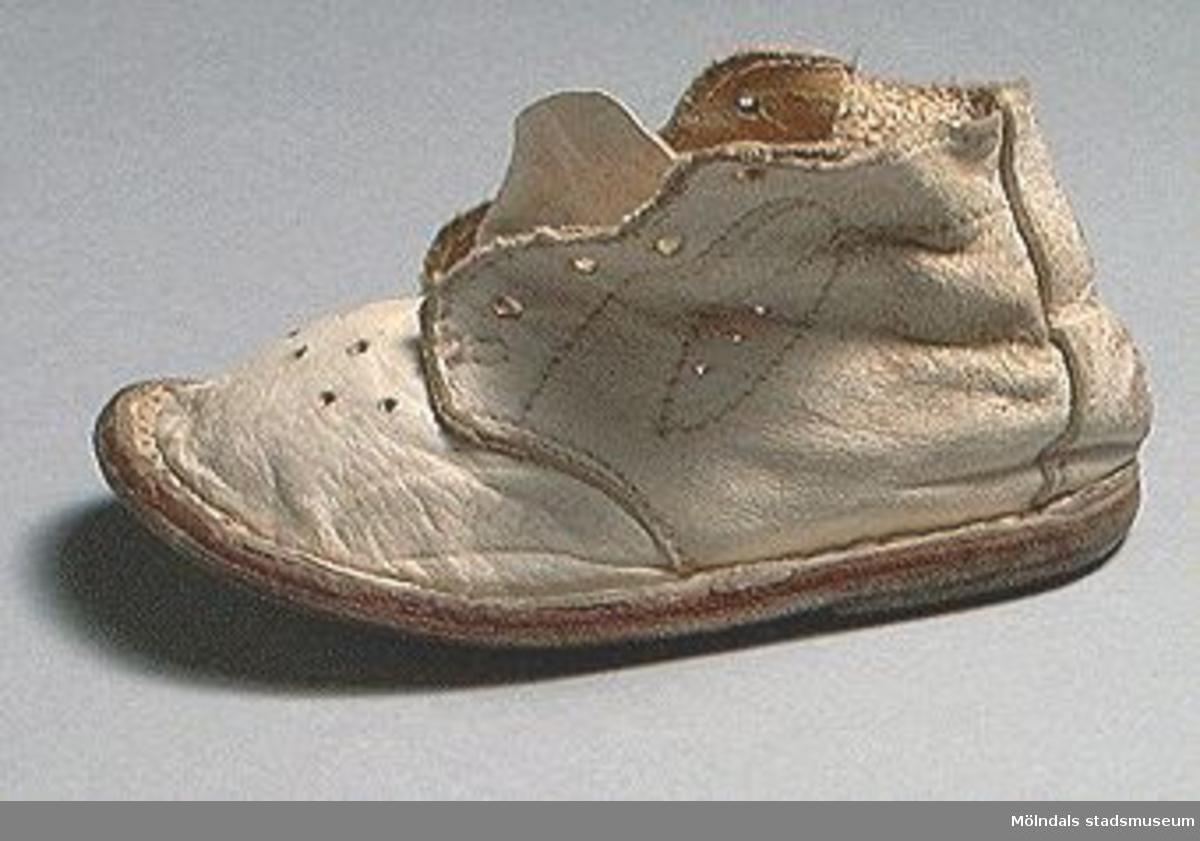 En vit babysko av läder. Snöre saknas.Sliten.