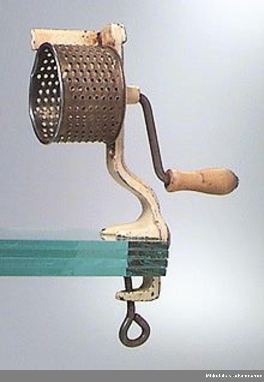 Mindre handvevat rivjärn av enkel konstruktion. Fint perforerad trumma vevas runt varvid det som skall rivas eller malas, pressas mot trummans utsida. Den anbringas vid bordskanten el. dyl. medelst klämskruv.Bredd med handvev: 155 mm.Tidigare sakord: grönsakskvarn.