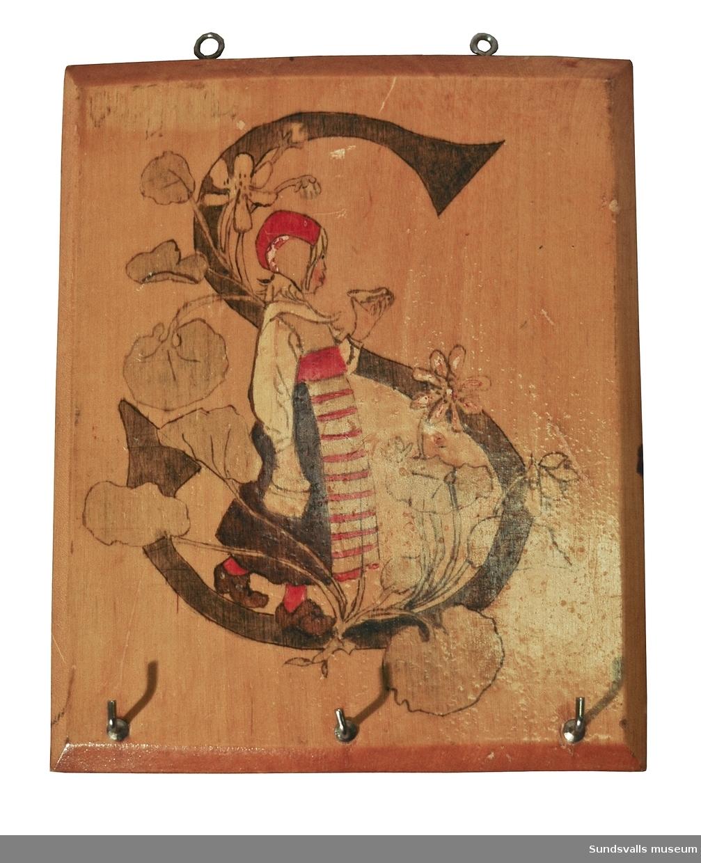 Handdukshängare i trä. Rektangulär platta med krokar i nederkanten och öglor i överkanten. Plattan är bemålad med ett motiv ur Jeanna Oterdahls 'Blommornas bok' (1905); en flicka i folkdräkt med ett 'S' som bakgrund, omgivet av en blomranka. Plattans målning är förnissad. Maria Rieck-Müller gjorde sådana handdukshängare till sina fem döttrar. Denna är gjord för dottern Sonja. Litt.: Maria Rieck-Müllers arkiv, Sundvalls Kommunarkivs samlingar, Medelpads arkiv.