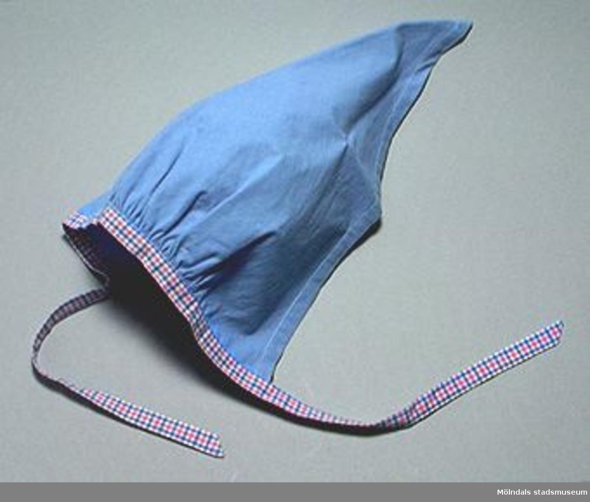 En skolkökssnibb i blått och rosablåvit-rutigt tyg. Med rynkning och 300 mm långa knytband. Undervisningsmaterial för årskurs 6. Samhör med 02663-02669. Övriga uppgifter se 02643:1.