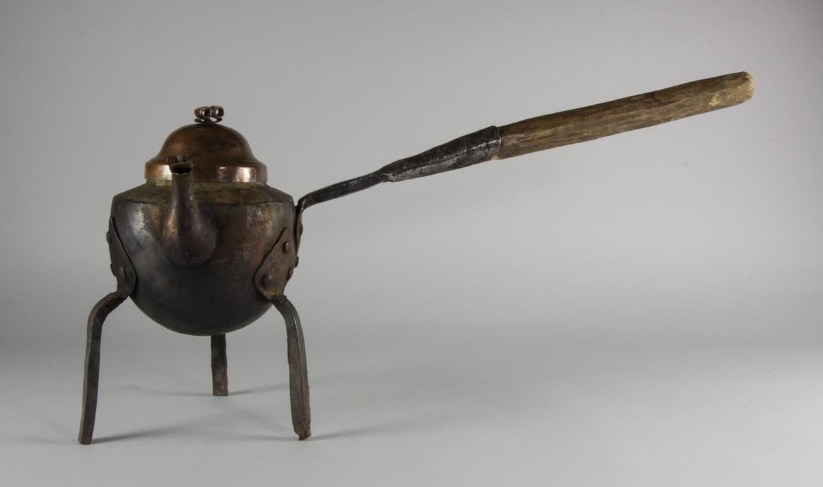 Kaffepanna tillverkad  av koppar. Lock med fals som ligger inuti pannan, knopp av rullad plåtbit. Svängd pip med fäste för lövformat lock. Handtag av järn med förlängning av trä. Förtent insida. Tre ben av järn med hjärtformade fästen, nitade.