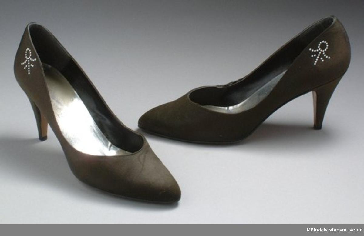 Brun/grå sko med hög klack. Bak på sidan sitter en liten silver utsmyckning.Måtten:Stl. 39, längd 270 mm, bredd 80 mm, höjd 150 mm (med klack).