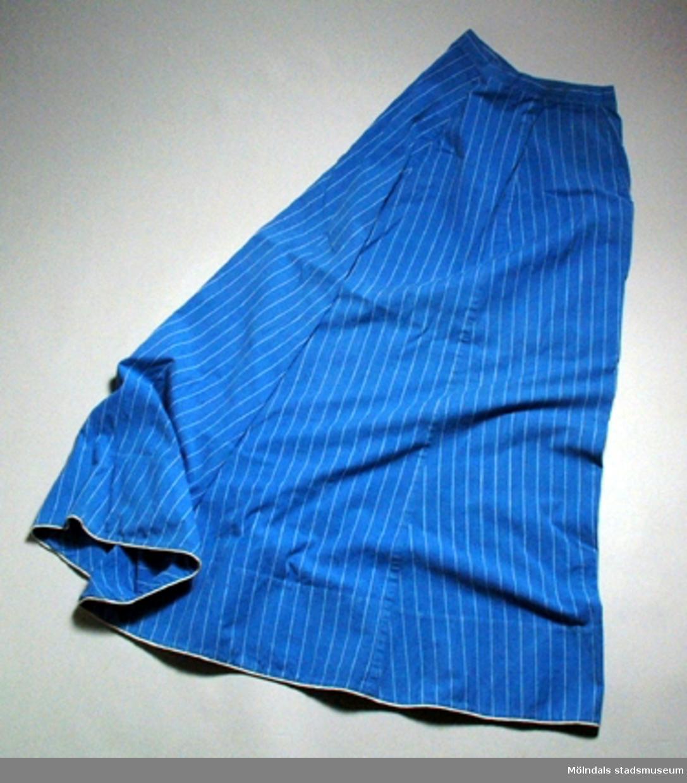 Blåvitrandig klänning i två delar med lagda stråveck. Band kantad nertill.Blus: Axelbredd 35 cm.       Ärmlängd: 61 cm.         Längd: 59 cm.Kjol: Midja 31 cm.        Längd: 110 cm.          Vidd nertill: 110 cm.