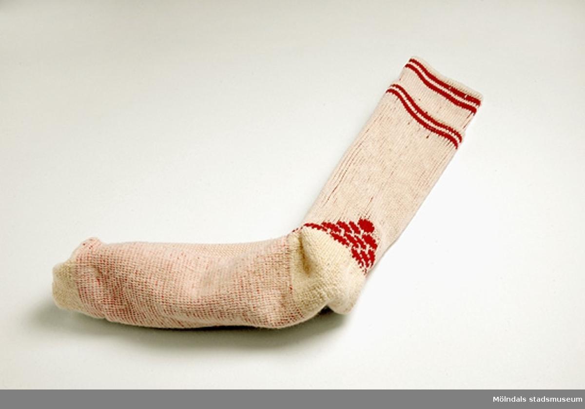 1 par ljusbeige bomullsstrumpor med två röda ränder upptill på strumpan. Slätstickad i foten och resårstickad vid vristen. Mönster vid hälen.Storlek 37-40.