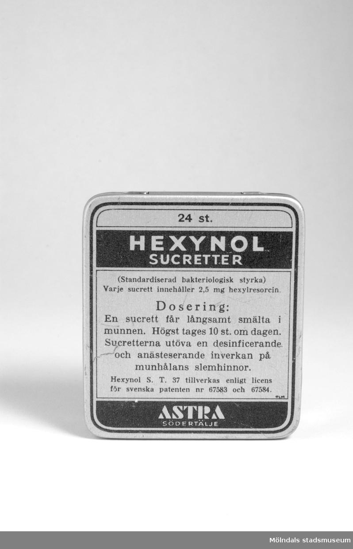 Fyrkantig medicinburk av plåt. Svart text. Innehöll Hexynol sucretter.