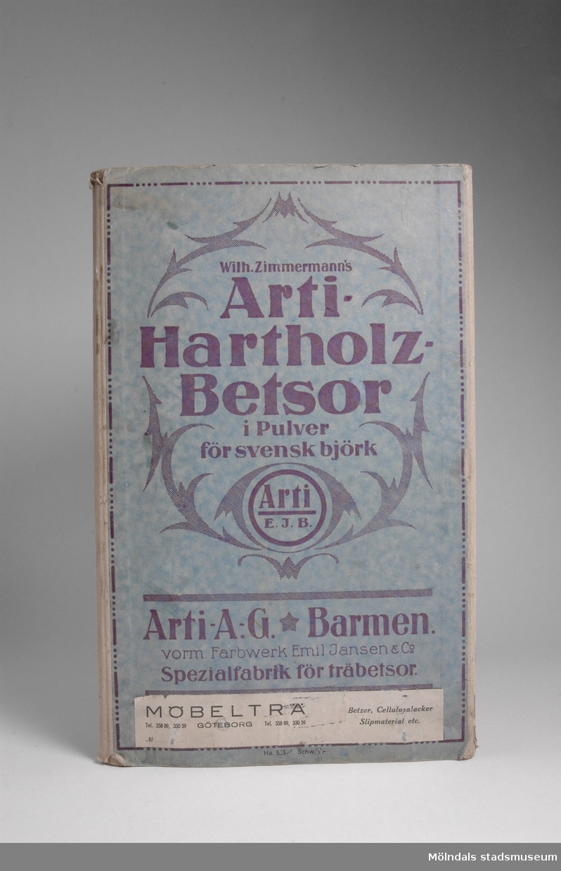 """Provkarta med möbelfärger från tyska Art A.G./Barmen, Specialfabrik för träbetsor.Redskap och verktyg kommer från Lindströms snickeri (Gamla Riksvägen 81, Ekebacken). Här byggde John Lindström från Lindome ett boningshus och snickeriverkstad 1928. Han öppnade ett snickeri som specialiserade sig på köksbord Borden levererades till en grossist i Göteborg. Som mest tillverkades 50-60 bord i veckan. Borden hade ben av björk och resten var av furu. Han gjorde även andra möbler på beställning. Till hjälp hade John ett par anställda.De sista åren gjordes mest renoveringar och reparationer, medan det """"begav sig"""" de mest aktiva åren tillverkades bord av alla de slag."""