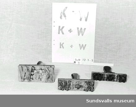 Stämpel i gummi med handtag i trä. Stämpeln visar bokstäverna K+W. Röda färgrester finns kvar på stämpeln.