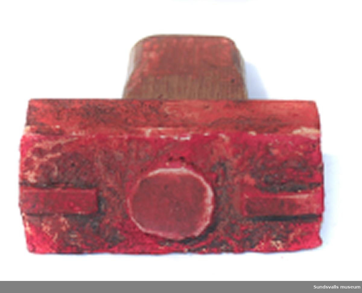 Stämpel i gummi med handtag i trä. Stämpeln visar avtryck '_._'. Röda färgrester finns kvar på stämpeln.