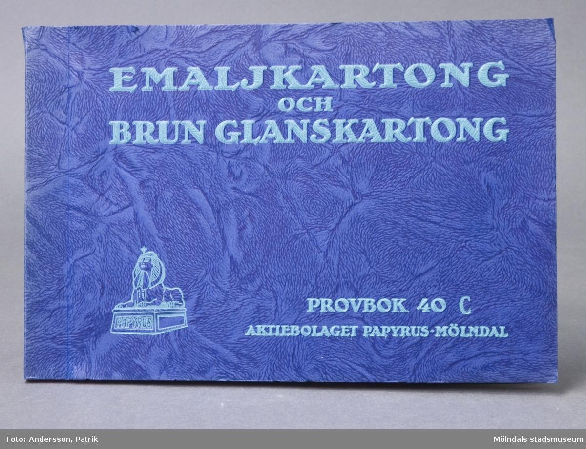 """Provbok 40C. Häfte med prover, """"Emaljkartong och Brun Glanskartong"""". Pärm av blå präglingsmönstrad kartong med grönt relieftryck. Logotyp med sfinx på fundament. Provark i olika färger. Produktinformation. Litteratur: Papyrus 1895-1945, Minnesskrifter, Esseltes Göteborgsindustrier AB, Göteborg 1945."""